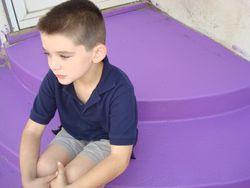 Samuel sits on purple chairs on the stairs outside my back door.