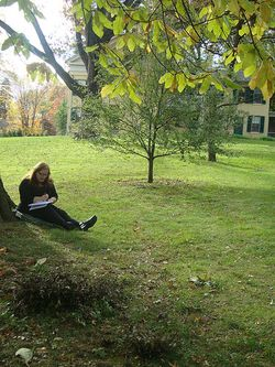 This is me, Julie Jordan Scott, writing in my notebook on the lawn of the house where Emily lived in Amherst, Massachusetts