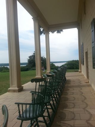 Chairs line the porch at Mt. Vernon. Great view of the Potomac