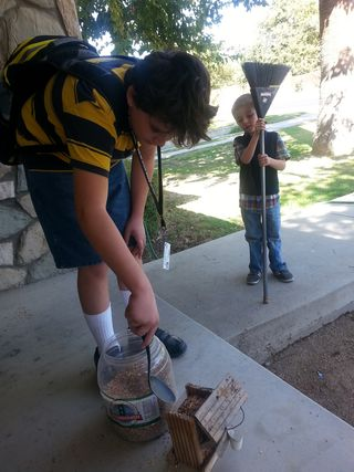 The boys took turns filling the bird feeder