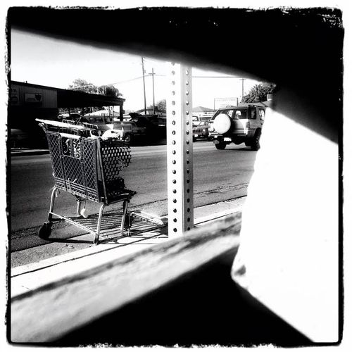 Shopping cart from behind the bench black and white