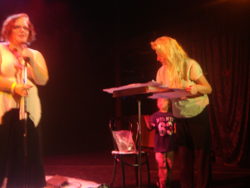 Julie Jordan Scott is at the Microphone writing a collaborative poem during a poetry performance