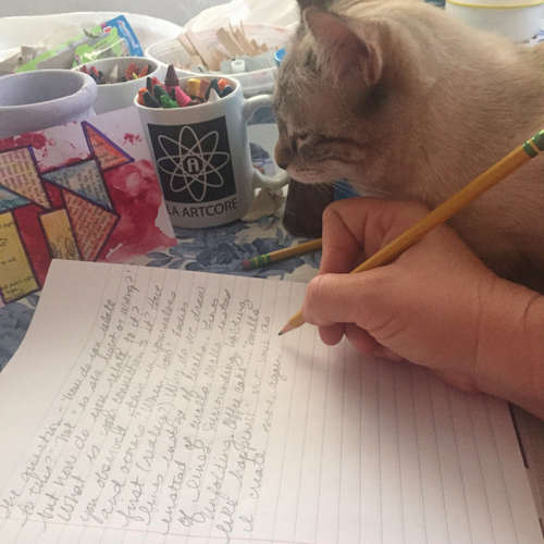 Alice my cat enjoyed sitting with me while I write. There is a piece of index card art next to my notebook.